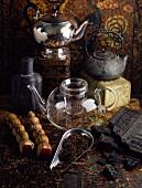 Tee-Stillleben mit verschiedenen Teekannen, Teeblättern und Ziegeltee