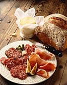Brotzeitteller mit Wurst und Schinken, dazu Brot und frische Butter