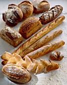 Verschiedene Brotsorten auf weißem Untergrund mit Mehl