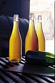 Flaschen mit Cidre, Holzfass im Hintergrund