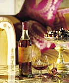 Cognac in Glas und Flasche mit Süssigkeiten auf dem Sofatisch