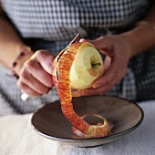 Frau schält einen Apfel