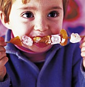 Child eating fruit kebab