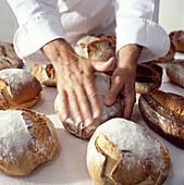 Bäcker mit vielen Brotlaiben
