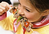 Child eating meat and pepper shish kebab