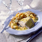Hake fillet in saffron-flavored sauce with mess of vegetables