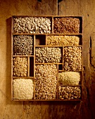 Verschiedene Getreidekörner in einem Setzkasten auf Holz