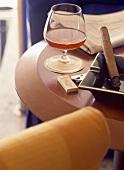 Ein Glas Cognac mit Zigarre auf kleinem Tisch mit Sessel