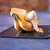 Bananas, one of them peeled