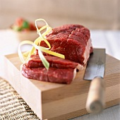 Raw roasting beef on chopping board with knife