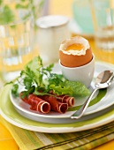 Soft-boiled egg and rolls of raw ham