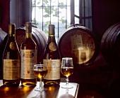 Italienische Weinflaschen mit Gläsern auf Holztisch, Holzfässer in Hintergrund