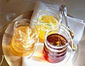 Aromatisiertes Öl und Essig in drei Gläsern