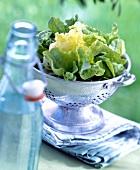 Grüner Salat im Abtropfsieb, Wasserflasche im Vordergrund