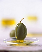 Grüne Olive mit Olivenöl beträufelt