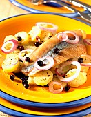 Marinated herring in oil with potatoes and juniper berries
