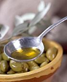 Schüssel mit grünen Oliven und Löffel mit Olivenöl im Vordergrund