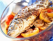 Baked bass with lemon, onions and tomatoes