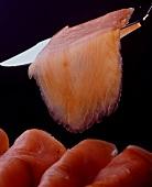 Räucherlachsröllchen und eine Scheibe auf Messer, schwarzer Hintergrund
