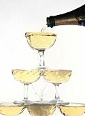 Champagner in eine Gläserpyramide gießen