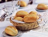 Brotkorb mit Baguettebrötchen auf dem Tisch mit Servietten, Gläsern und Besteck