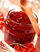 Pot of redcurrant jelly with wooden spoon (topic: summer fruits)