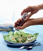 Seasoning salad on table with hands