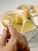 Cheese fondue with cubes of bread and hand