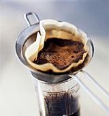Frisch gebrühter Kaffee wird in ein Glas gefiltert