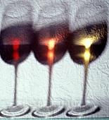 Drei Weingläser mit Weiss-, Rosé und Rotwein hinter transparentem Tuch
