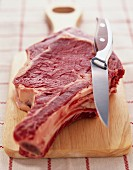 Raw rib of beef on chopping board with knife