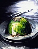 White fish mousse dome covered with green cabbage leaves and truffles