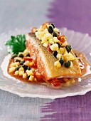 Piece of salmon cooked on one side with crushed vegetables, apples and capers
