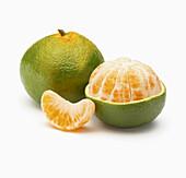 Zwei Pomelos, davon eine geschält