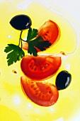 Tomatenscheiben, Oliven und Petersilie in Olivenöl