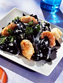 Squid ink spaghettis with scampis and herbs