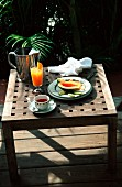 A breakfast table outside with tea, fruit and orange juice