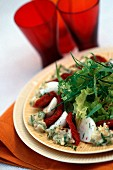 A green salad with dried tomatoes, mozzarella and chilli