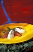 Goat's cheese dumplings with dried tomatoes and basil on a bright yellow plate
