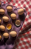 Eggs in an egg box in a red, checked table cloth