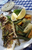 Grilled branzini with herbs and vegetables