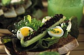 Celery filled with tapenade, quail's eggs and lettuce leaves on grilled bread