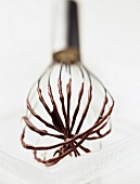 Whisk with melted chocolate