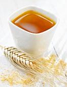 Weizenkeimöl in einem Schälchen mit Weizenähre