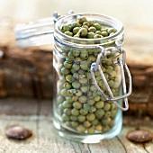 Small glass jar of green peppercorns