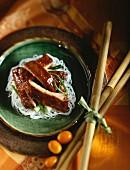 Glasiertes Schweinefleisch auf Reisnudeln