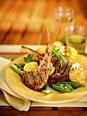 Gegrillte Lammkoteletts mit Mais und Erbsenschoten