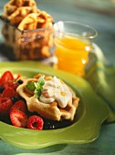 Waffles with orange cream on red berries