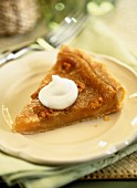 A slice of walnut tart with maple syrup