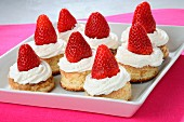 Cookies topped with cream and strawberries